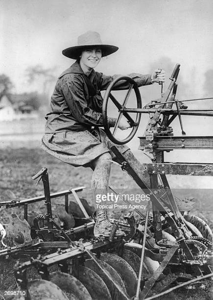 A mud splattered student from Vassar College works as a land girl driving a tractor attached to a plough to contribute to America's war effort during...