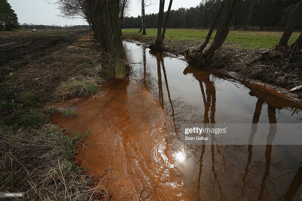 Mud tinted orange due to a high content of iron sediment lies in the Wudritz creek in the Spreewald region on April 17, 2013 near Luebbenau, Germany. The Wudritz is heavily burdened with iron from the nearby former Schlabendorf open pit coal mine, which has since been turned into a lake called the Schlabendorfer See. Many creeks and small rivers that feed the Spree River have turned a rich orange or brown, sometimes even red, due to the sediments flowing from several former open pit coal mines. The Spreewald is a popular tourist destination known for its network of canals and local tour operators fear the sediment will turn the waters there orange as well, which could seriously impact the tourist seasons. Though the iron sediment is not poisonous, some local farmers claim they have been forced to filter the water they use to irrigate their fields, and many people report the disappearance of fish and other fauna.