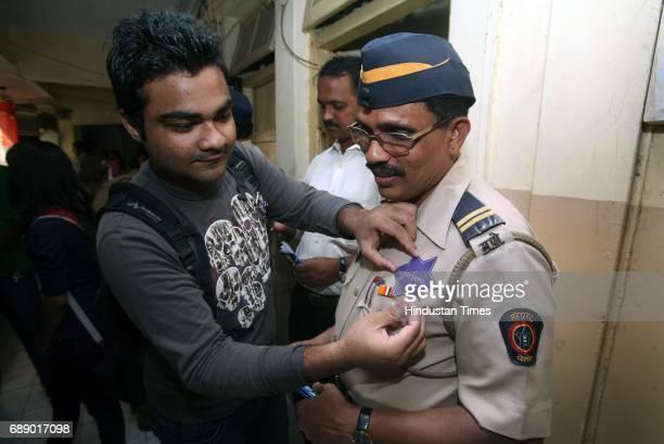 Mudassir Mozawala sticks a sticker saying Superhero on Police Naik Bhagwan Kadam Students of Rotaract Club of Lala Lajpatrai College thanked the...