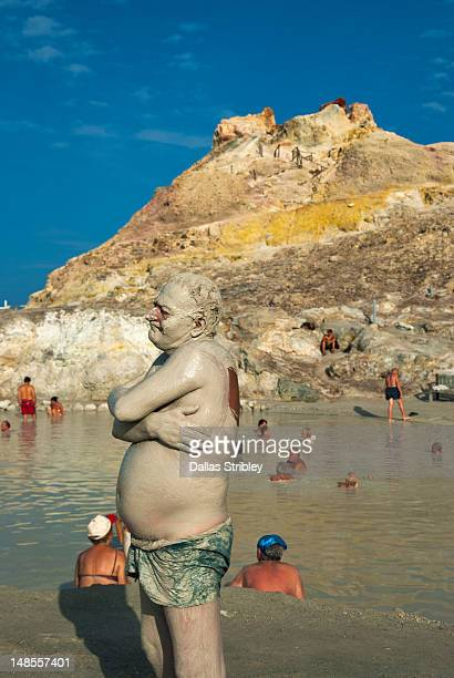 Mud-covered man at the therapeutic volcanic thermal mud pool, Levante Beach.