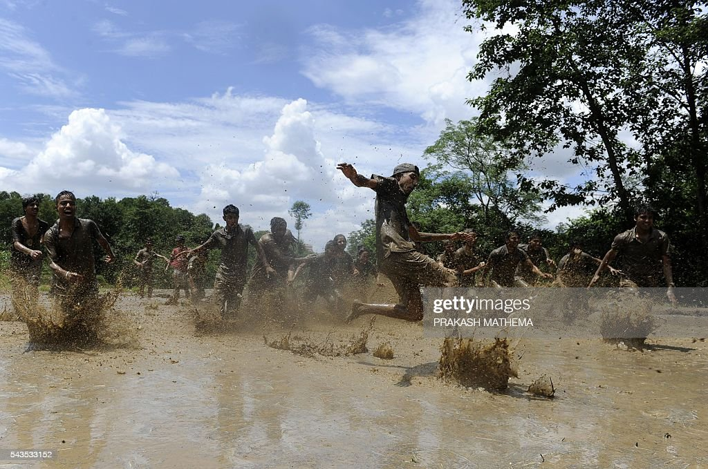 Mud-covered Nepalese youths play in a rice paddy field in Baande village on the outskirts of Kathmandu on June 29, 2016. Farmers in Nepal celebrate National Paddy Day as the annual rice planting season begins. / AFP / PRAKASH