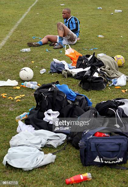 A muddy and injured Sunday League footballer watches his teammates play after being substituted during his team's match on the Hackney Marshes'...