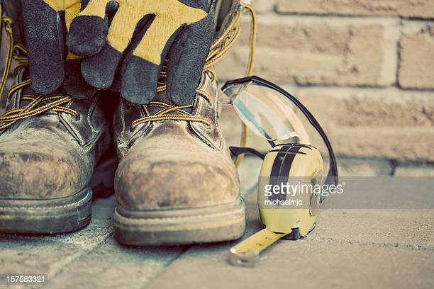 Muddy construction work boots with gloves and tape measure