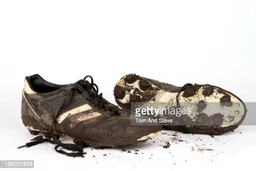 Muddy football boots on a white background