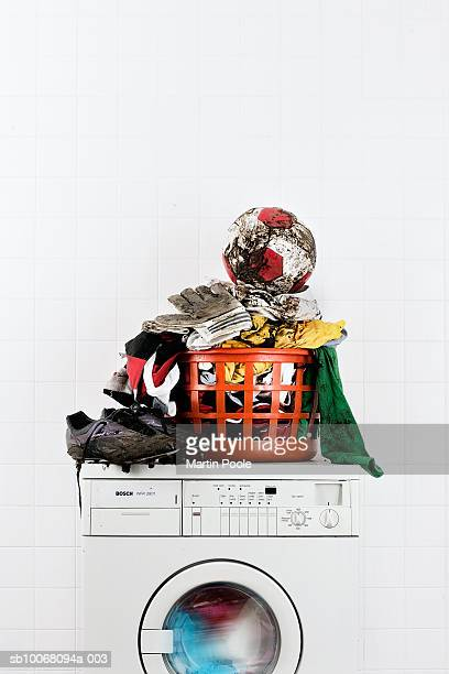 Muddy football kit with ball and boots in laundry basket on washing machine