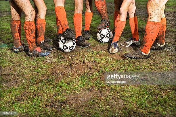 Muddy legs of soccer players