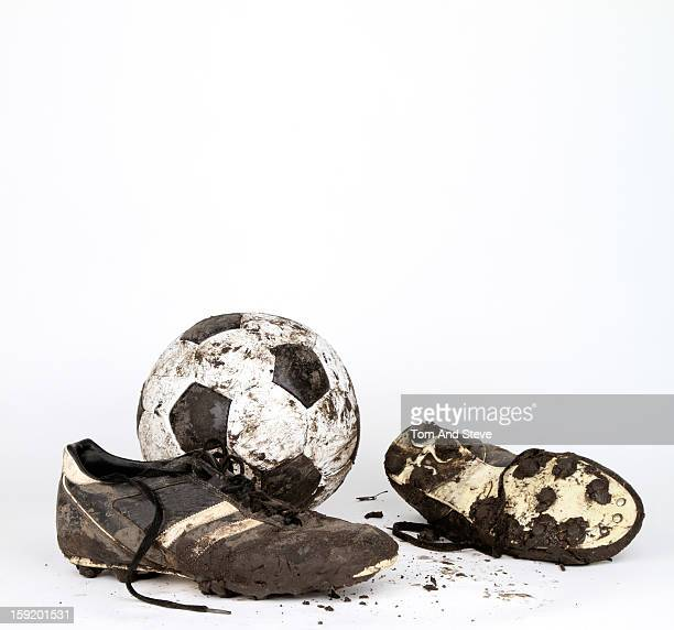 Muddy soccer boots and a football, with copy space