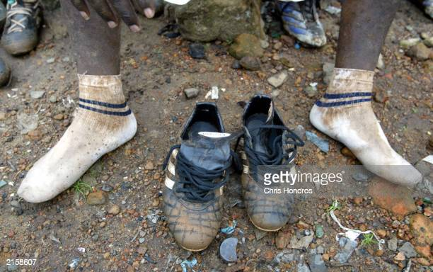 Muddy socks and shoes of a Liberian soccer player sit on the ground during halftime at an intramural soccer match July 13 2003 in Monrovia Liberia...