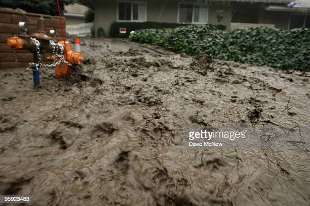 Muddy water and debris flow as heavy rain falls in an evacuated neighborhood during the fourth storm of the week on January 21 2010 in La Canada...