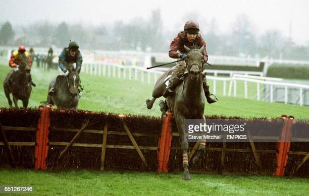 A mudsplattered Thierry Doumen on Bilboa clears the last fence on his way to winning The Glenlivet Anniversary 4YO Novices' Hurdle Race