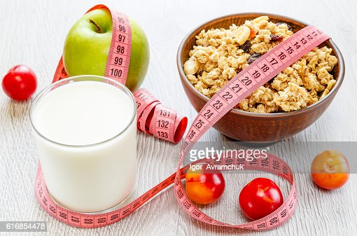 Muesli milk meter tape on wooden background : Stock Photo