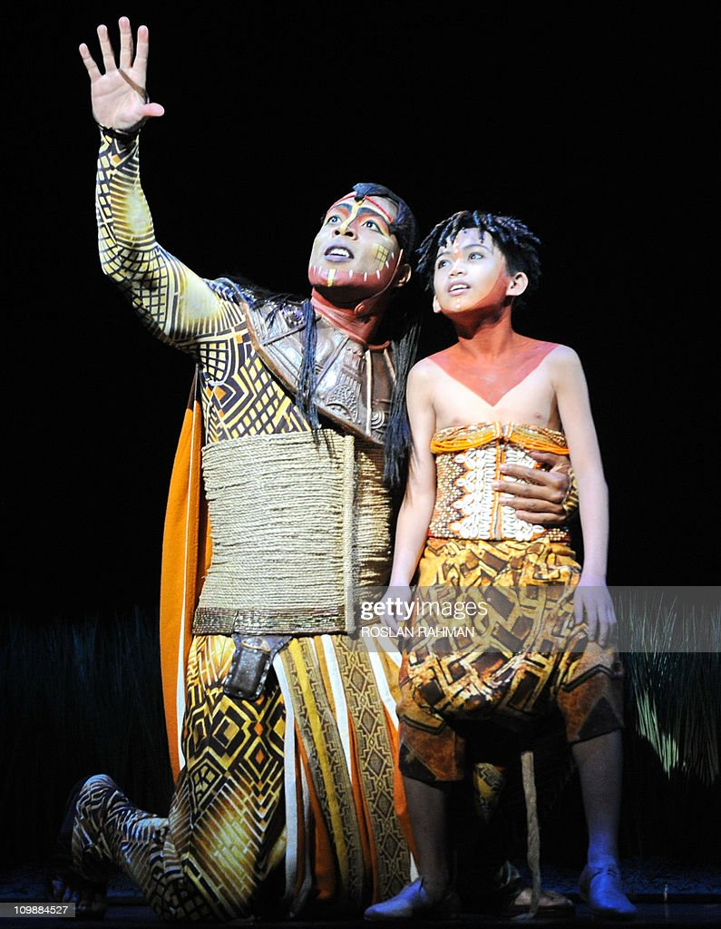 Mufasa, played by Jee-L Guizonne (L) of France and Young Simba, Leon Matawaran (R) of the Philippines perform during a media preview of the Lion King musical performance in Singapore on March 9, 2011. The award-winning broadway musical event, the Lion King celebrates its debut in Southeast Asia at the Marina Bay Sands theatre on March 10.