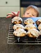 Toddler reaches up to grab a freshly baked muffin