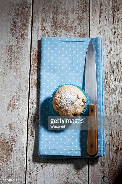 Muffins, knife and cloth on wood