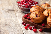 muffins with cranberries, cranberries in a glass bowl on the old wooden background