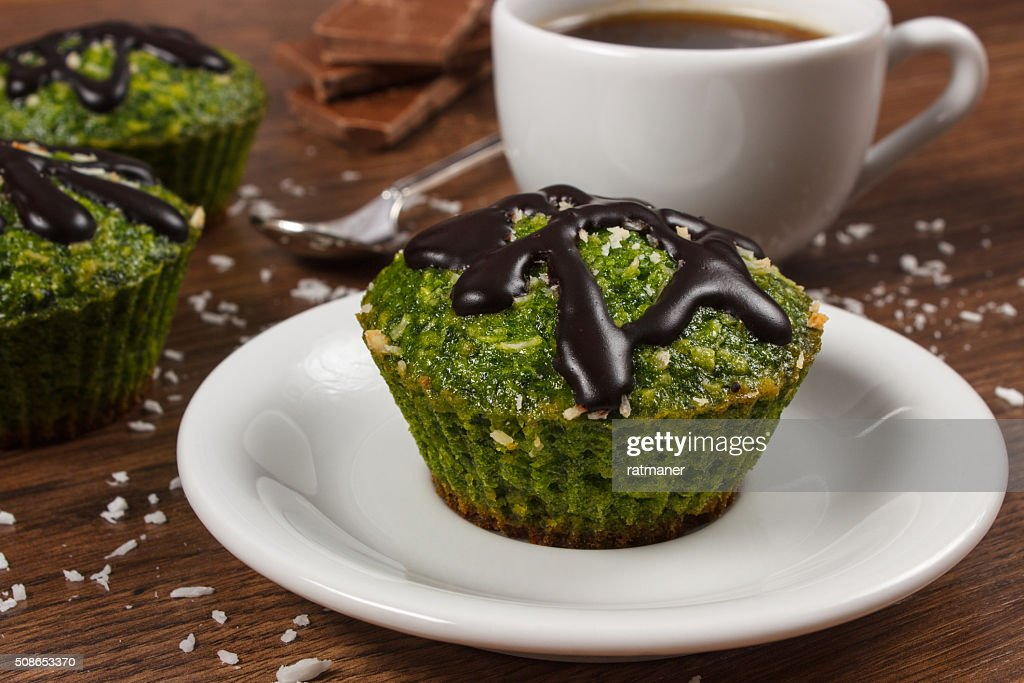 Muffins with spinach, desiccated coconut, chocolate glaze, cup of coffee : Stock Photo