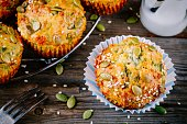 muffins with spinach,  feta cheese pumpkin seeds and sesame seeds on wooden background