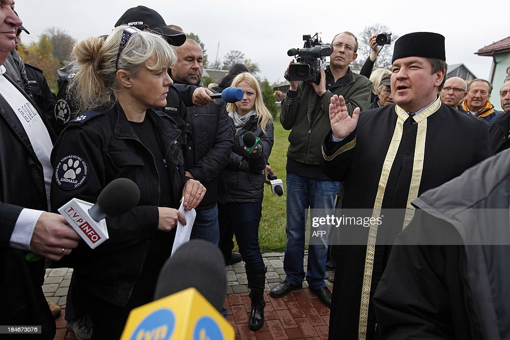 Mufti of Poland Tomasz Miskiewicz (R) speaks to animal rights activists and to reporters gathering outside the mosque in Bohoniki village, eastern Poland, on October 15, 2013. Polish Muslims began the celebration of the Eid al-Adha, Feast of the Sacrifice, one of the two most important feasts in the Muslim religion. On this occasion of the religious holiday, Polish muslims planned to ritually slaughter a few lambs. Animal rights activists protested outside the Mosque in Bohoniki, arguing that ritual slaughter is forbidden by law in Poland.