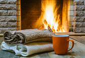 Mug  for tea or coffee, wool things near  cozy fireplace, in country house, winter vacation.