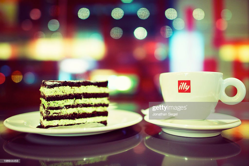 Mug of illy coffee served alongside a slice of mint cake in a stylish, colorful cafe.