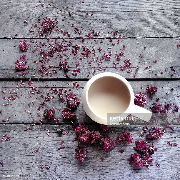 Mug of tea surrounded by dried flower blossoms