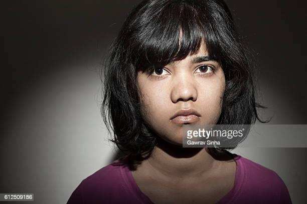 Mug shot of an unhappy teenage girl looking at camera.
