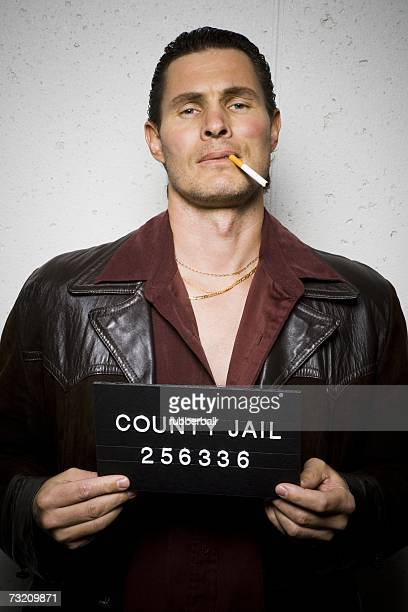 Mug shot of man with cigarette and gold chains