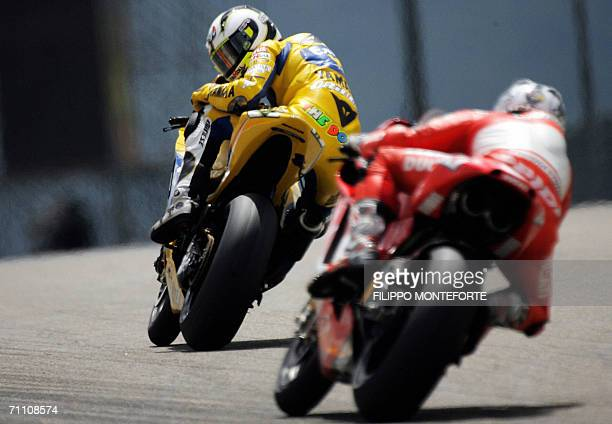 Italy's Valentino Rossi looks backwards at Spain's Sete Gibernau during the second practice session of the Italian MotoGP Grand Prix at Mugello's...