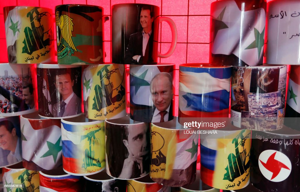 Mugs displaying portraits of Syrian President Bashar al-Assad and his Russian counterpart Vladimir Putin are seen in central Damascus on April 7, 2017. US forces fired a barrage of cruise missiles at a Syrian airbase in response to what President Donald Trump called a 'barbaric' chemical attack he blamed on the Damascus regime. / AFP PHOTO / Louai Beshara