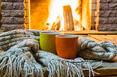 Mugs  for tea or coffee,  wool things near cozy fireplace, in country house, winter vacation, horizontal.
