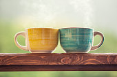 Mugs with a hot drink with tea on a wooden stand outdoors in the countryside