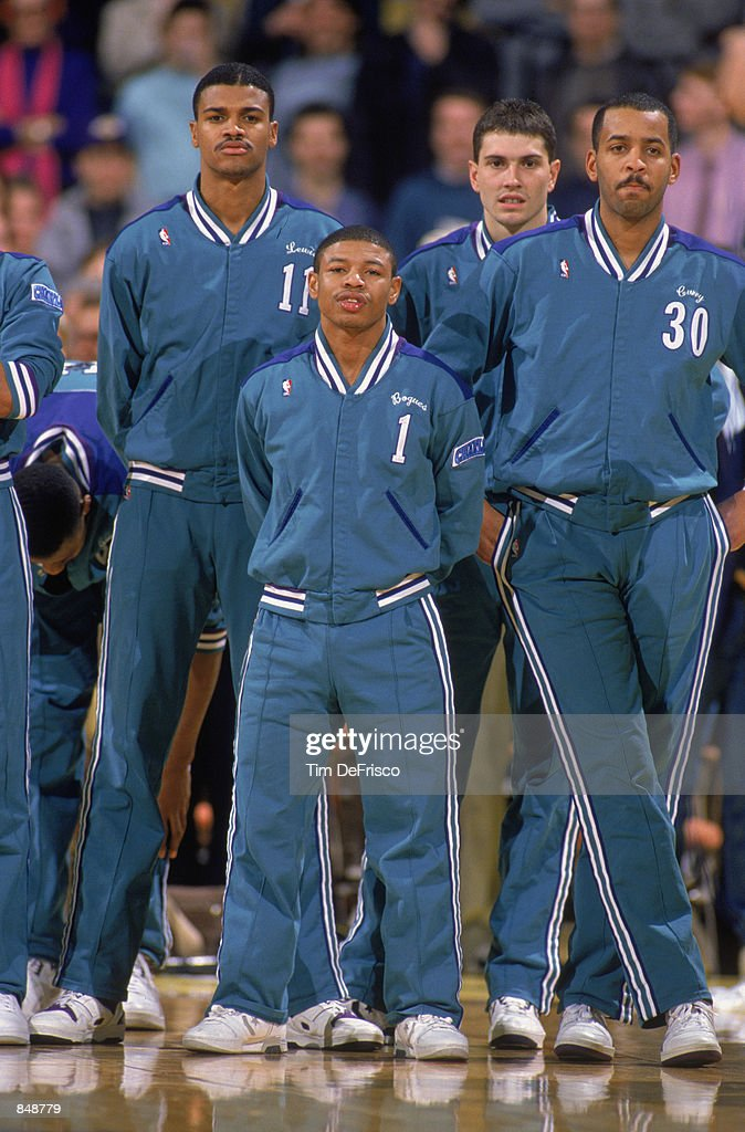 Mugsy Bogues of the Charlotte Hornets stands with his teammates before an NBA game at Charlotte Colesium in 1989