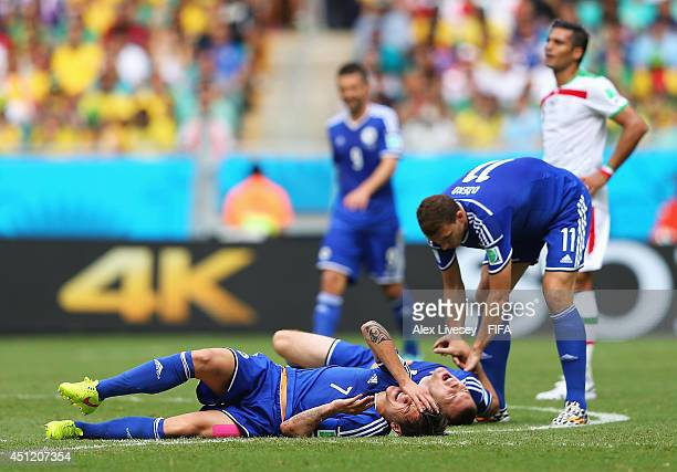 Muhamed Besic of Bosnia and Herzegovina and his teammate Toni Sunjic lie on the ground injured after colliding while Edin Dzeko help them during the...