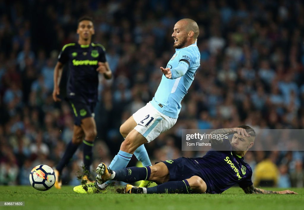 Muhamed Besic of Everton tackles David Silva of Manchester City during the Premier League match between Manchester City and Everton at Etihad Stadium on August 21, 2017 in Manchester, England.