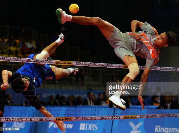 Muhammad A'fif of Singapore jumps for the ball against Pornchai Kaokaew of Thailand during the men's team sepaktakraw preliminary round match at the...