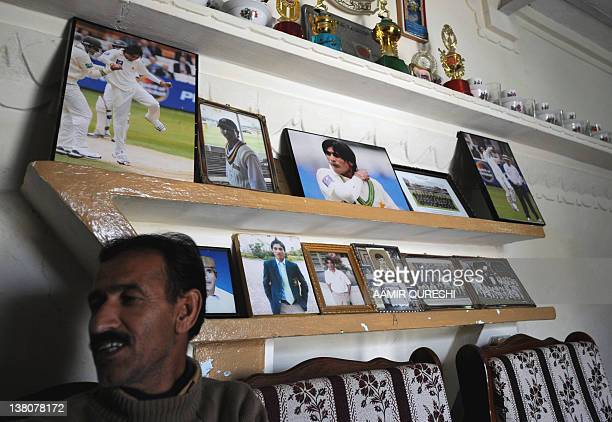 Muhammad Ashraf brotherinlaw of former Pakistani cricketer Mohmammad Aamer sits in front of photographs of Aamer displayed in a room at the family...
