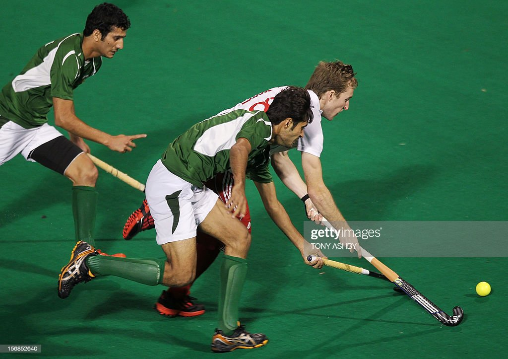 Muhammad Rizwan Jr. of Pakistan (C) chases Barry Middleton of England (R) as he moves to score a goal during their men's match on day two at the International Super Series hockey tournament in Perth on November 23, 2012. AFP PHOTO/Tony ASHBY RESTRICTED