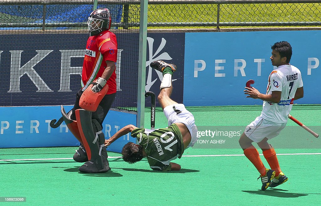 Muhammad Rizwan of Pakistan (C) tumbles after attempting to score as goalkeeper T.R. Potnuri (L) and Manpreet Singhof (R) of India look on during their match on the final day of the International Super Series hockey tournament in Perth on November 25, 2012. AFP PHOTO / Tony ASHBY IMAGE