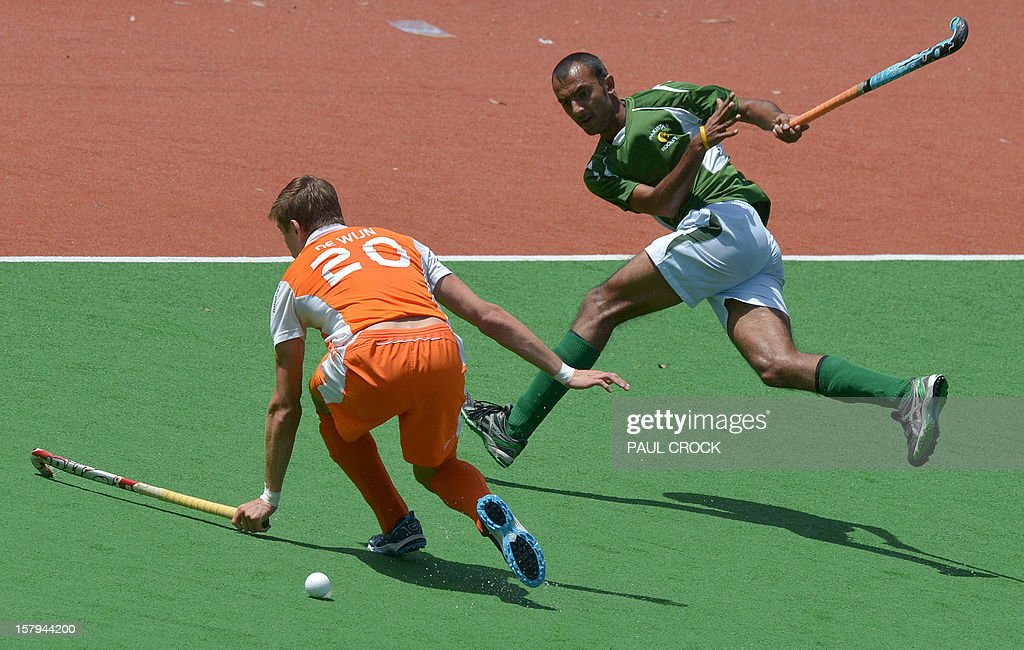 Muhammad Umar Bhutta of Pakistan (R) makes a pass through Sander de Wijn of the Netherlands during their semi final match at the Men's Hockey Champions Trophy in Melbourne on December 8, 2012. IMAGE STRICTLY RESTRICTED TO EDITORIAL USE - STRICTLY NO COMMERCIAL USE AFP PHOTO/Paul CROCK