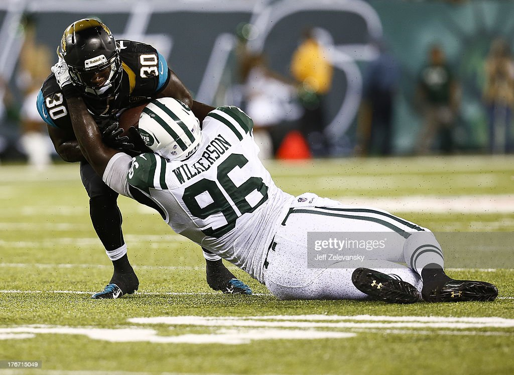 Muhammad Wilkerson #96 of the New York Jets pulls down Jordan Todman #30 of the Jacksonville Jaguars during their preseason game at MetLife Stadium on August 17, 2013 in East Rutherford, New Jersey.