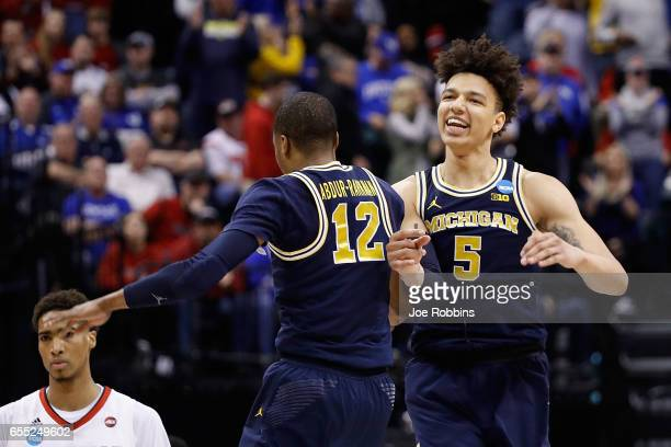 MuhammadAli AbdurRahkman and DJ Wilson of the Michigan Wolverines celebrate in the second half against the Louisville Cardinals during the second...