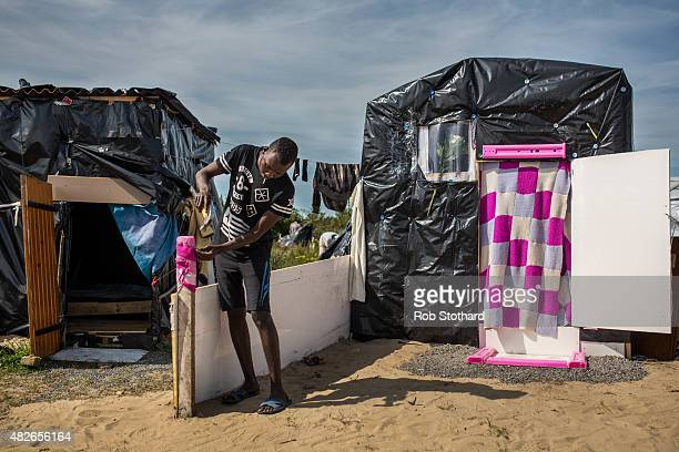 Muher from Sudan adds a dividing wall outside his tent in a make shift camp near the port of Calais on August 1 2015 in Calais France Migrants are...