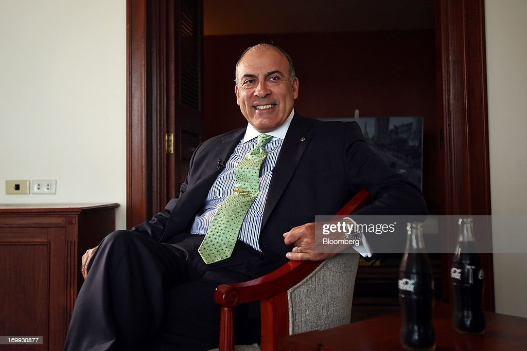 Muhtar Kent, chief executive officer of Coca-Cola Co., sits next to bottles of Coca-Cola soda during a Bloomberg Television interview in Yangon, Myanmar, on Tuesday, June 4, 2013. Kent marked the return of the world's largest soda maker to Myanmar after 60 years by opening a bottling plant and pledging more investment in the newly opened economy. Photographer: Dario Pignatelli/Bloomberg via Getty Images