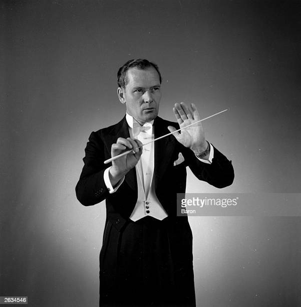 Muir Mathieson the British conductor film score composer and director of musical documentaries pictured while conducting Original Publication People...