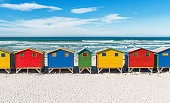 Symmetric landscape of Muizenberg beach with its famous colorful beach huts and surfers paradise near Cape Town, South Africa.