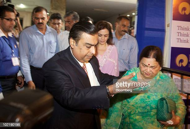 Mukesh D Ambani chairman of India's Reliance Industries Ltd left arrives with his mother Kokilaben to the company's annual general meeting in Mumbai...