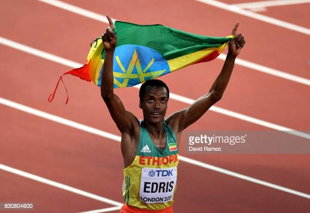 Muktar Edris of Ethiopia celebrates with an Ethiopian flag after winning gold in the Men's 5000 Metres final during day nine of the 16th IAAF World...