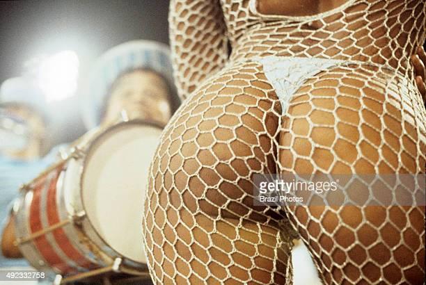 Mulatto sensual woman wearing bikini and dancing at Samba Schools Parade Rio de Janeiro carnival Brazil musical instrument cuica in background