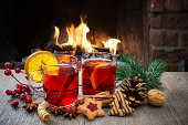 Delicious mulled wine with christmas decoration at romantic fireplace