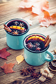 Mulled wine in blue enameled rustic mugs with spices and citrus fruit on wooden table with autumn leaves. Retro toned.